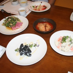Tofu nero con insalata, gingseng e semi neri, insalata di calamari e carote, kimchi