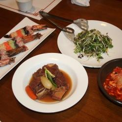 Gal-bi costine di carne, insalata con germogli di soia, gamberoni ripieni di uova di pesce e l'immancabile kimchi